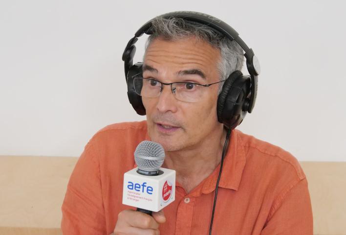 Photo d'Alain Trintignac tenant un micro aux couleurs de l'AEFE