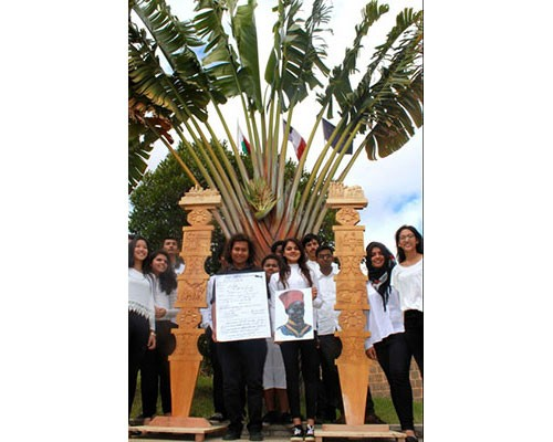 Lycée français de Tananarive (Madagascar).<br /> Contre-plongée sur des élèves de Tananarive rassemblés autour de deux sculptures traditionnelles en bois dont les gravures représentent la vie du soldat malgache Rafiringa, mort au combat, loin de sa terre natale.
