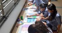 Des élèves de l'école Voltaire du Caire peignent sur des photographies d'immeubles pendant une APP sur le développement durable