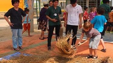 Les gestes du battage du riz dans la cour du lycée de Bangkok.